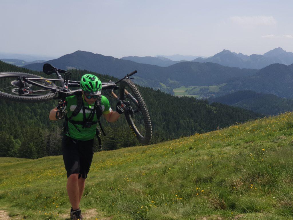 Mountainbiker bär cykel