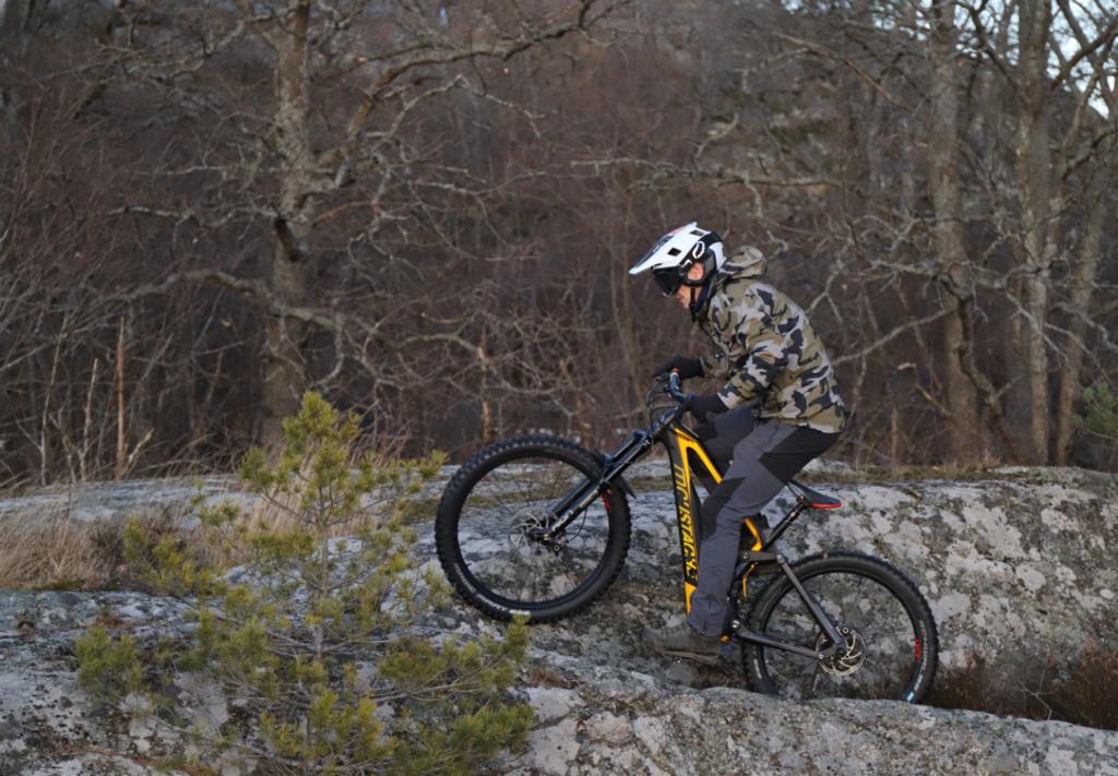 Mountainbiker cyklar uppför klippa