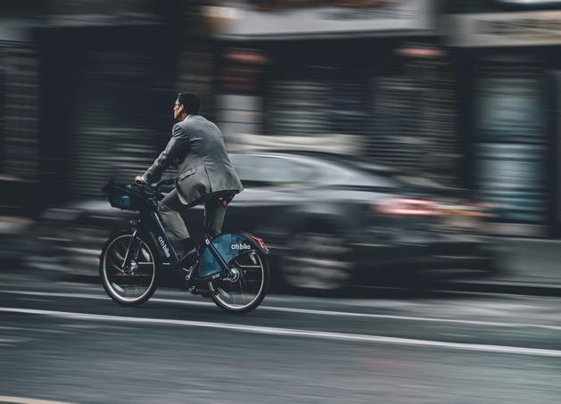 affärsman som cyklar snabbt utan hjälm
