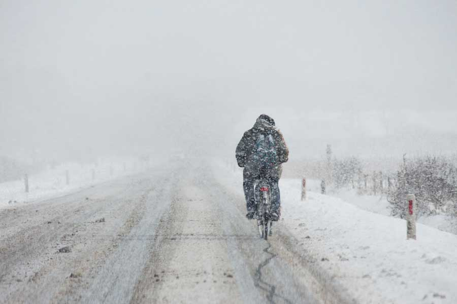man cyklar i snömodd