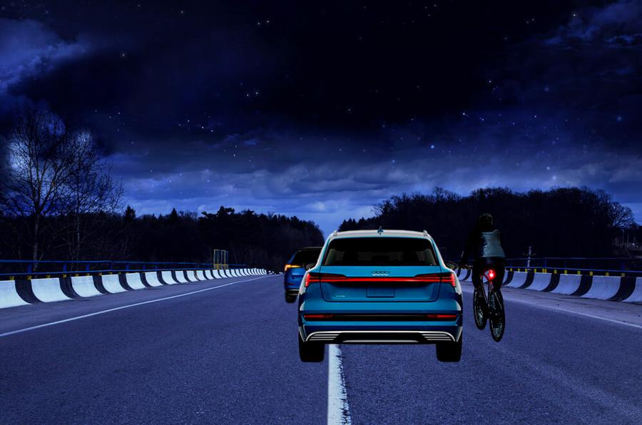 cyklist utan baklampa på hjälmen dyker upp bakom bil